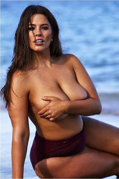 Oh Ya, her is Ashley Graham sittingon the beach topless with nothing but her arm covering her bust, This plus size bikini model is simply stunning. So HOT