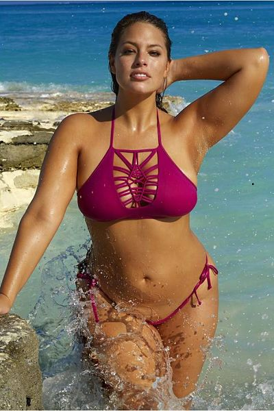 A stunning cross laced purple top on Ashley Graham with a matching purple string thong bikini bottom, splashing in the ocean waves.