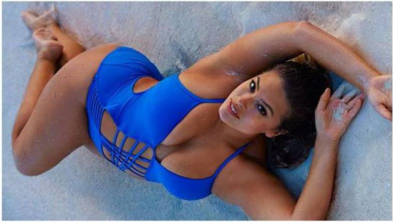 Ashley Graham in a sexy Lcae up one piece blue thong swmsuit