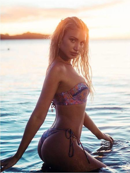 A sexy pic of Gabrielle Epstein in the ocean at sunset wearing a cheeky scrunch bottom bikini