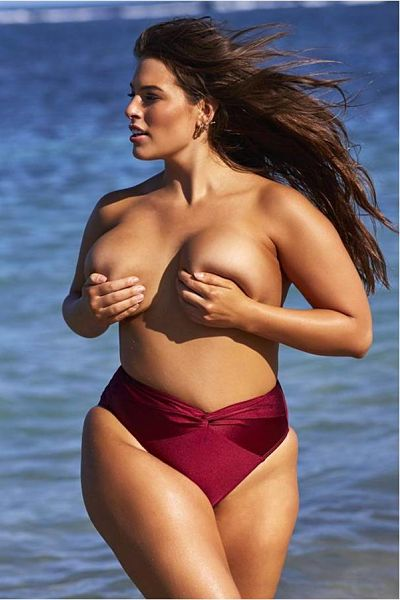 Topless again, Ashley Graham strolls down the beach topless with nothing covering her breasts except her hands. Such a sexy photo. Her bottom is a wrapped high waist thong bikini