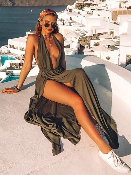 Another shot of Gabby taking it easy on the rooftop waering a long maxi dress with deep plunging neckline and hip length side split showing some leg and thigh for the camera
